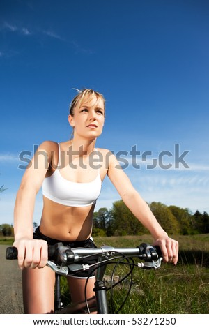 A sporty woman riding a bicycle outdoor