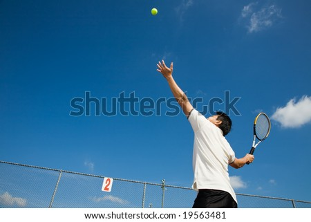 A sporty young asian male playing tennis - stock photo