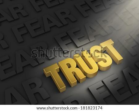 "A spotlight illuminates a bright, gold ""TRUST"" on a dark background of ""FEAR""s - stock photo"