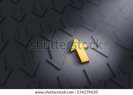 A spotlight illuminates a bright, gold up arrow on a dark gray background filled with down arrows.  - stock photo