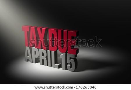"""A spotlight illuminates a shiny bold, red """"TAX DUE"""" atop a dark gray """"APRIL 15"""" on a dark background. - stock photo"""