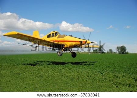 A spray plane flies low over a field. - stock photo