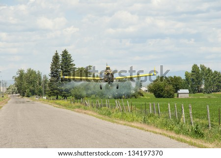 A spray plane flies over a farm and fenced fields on the High Desert of Idaho. - stock photo