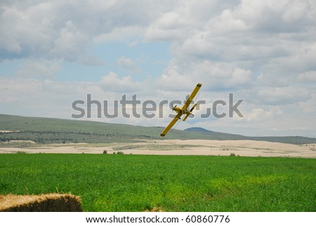 A spray plane pulls up and banks over an alfalfa field. - stock photo