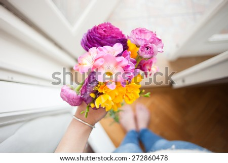 A spring gift: hand holding a bouquet of spring flowers - stock photo