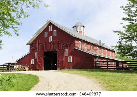 A springtime image taken on the trail leading to the open doors of a big red barn on a sunny day.