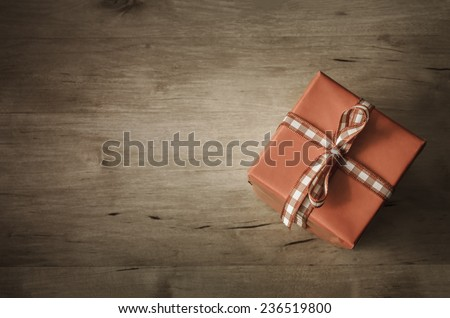 A square gift box, set at an angle and tied with gingham check ribbon, shot from above on wooden planked table.  Vintage style colouring and vignette applied.  Copy space on left side. - stock photo