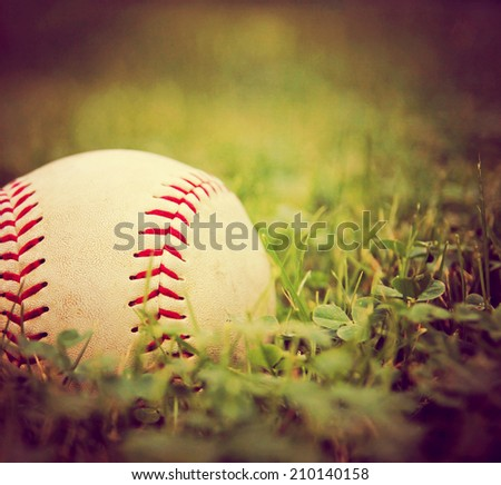 a square photo of a baseball in a grass background toned with a vintage retro instagram filter - stock photo
