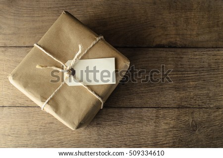 A square shaped parcel, wrapped in brown paper and tied with string.  Blank label tag and oak wood planking provide copy space.
