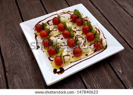 A square white plate with sticks of cherry tomatoes, Italian Mozarella cheese balls and fresh basil leaves topped with olive oil and balsamic vinegar served as starter on an old wooden table outside.