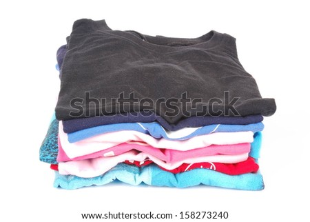A stack of a boys ironed t-shirts in various colors. Image isolated on white studio background. - stock photo