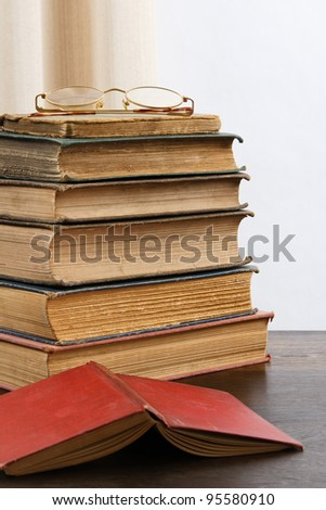 A stack of aged antique books with eyeglasses on top and an open red hardcover book in the foreground. - stock photo