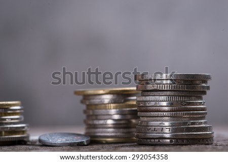 A stack of assorted coins on the wooden table
