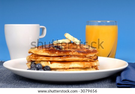 A stack of blueberry pancakes with coffee and orange juice - stock photo
