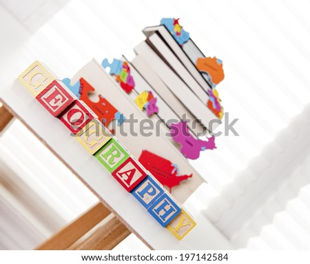 A stack of books and blocks spelling the word geography sit on a table.