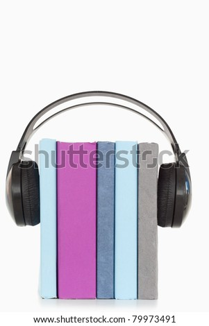A stack of books and headphones against a white background - stock photo