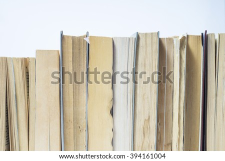 A stack of books in hard and soft cover. Book background - stock photo