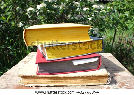 A stack of books in the garden - stock photo