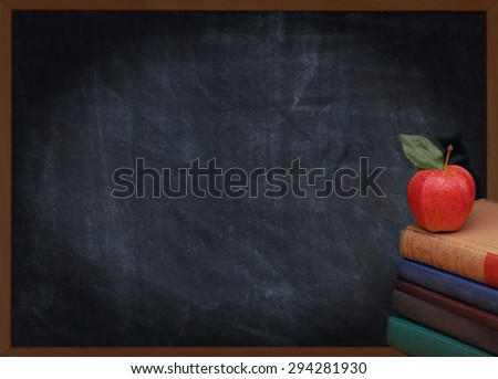 A stack of books with a red apple on top in front of an out of focus chalkboard. Back to school or education concept. Vintage effect with vignette added.  - stock photo