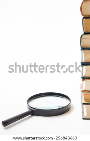 A stack of books with magnifying glass on white background - stock photo