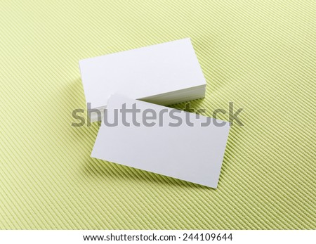 A stack of business cards on a green background. Template for branding identity. - stock photo