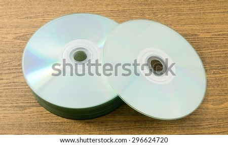 A Stack of CD or DVD Compact Disc on A Wooden Table. - stock photo