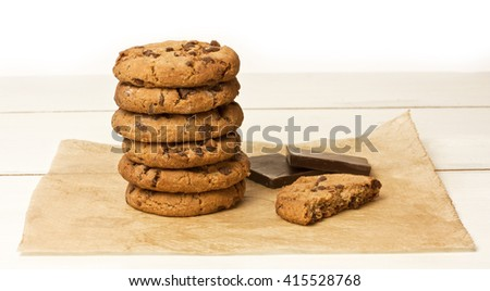 A stack of chocolate chips cookies and a half of one, with a couple of pieces of dark chocolate, on a sheet of baking paper, with copyspace - stock photo