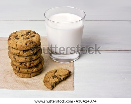 A stack of chocolate chips cookies on baking paper, with a glass of milk, with a half of a cookie, on a light wooden background texture, with copyspace; healthy breakfast concept - stock photo