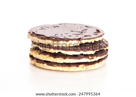 A stack of chocolate coated rice cakes on white background - stock photo