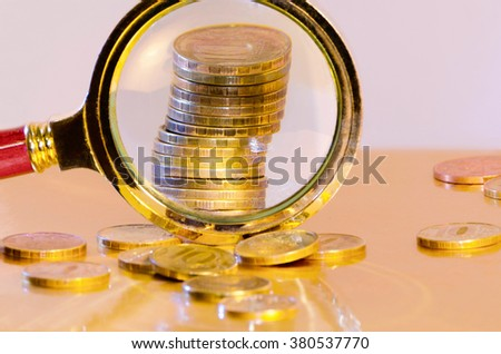A stack of coins, increased under a magnifying glass - stock photo