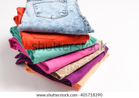 A stack of colored jeans isolated on white background - stock photo
