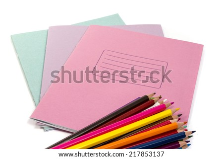 A stack of colored pencils lying on top of a stack of three copybooks on white background