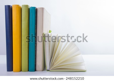 A stack of colorful books and open book. Ideas for business and self-development isolated on white background with empty place for your text - stock photo