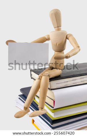 A stack of colorful books, open book. Wooden mannequin holding business card placard sitting on the stack of colorful books.  - stock photo