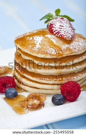 A stack of 6 cooked plain pancakes with fruit