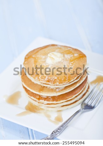 A stack of 6 cooked plain pancakes with melting butter - stock photo