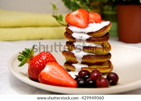 A stack of delicious pancakes on a light ceramic plate drizzled with whipped cream sauce with fresh berries, black currants, gooseberries and ripe strawberries. close-up - stock photo