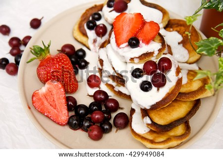 A stack of delicious pancakes on a light ceramic plate drizzled with whipped cream sauce with fresh berries, black currants, gooseberries and ripe strawberries. Top view, close-up - stock photo
