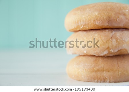 A stack of donuts on a white wooden table with a robin egg blue background. Vintage style. - stock photo