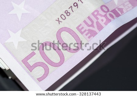 A stack of euro banknotes with a rubber band.