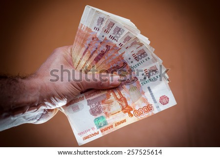 A stack of five thousand bills in the men's hands. - stock photo