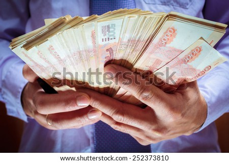 A stack of five thousandth bills in the men's hands. - stock photo
