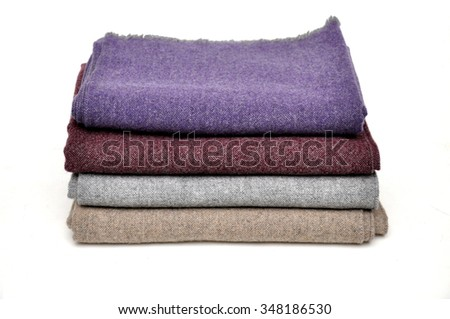A stack of folded scarves isolated on white background. - stock photo