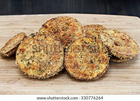 A stack of fried eggplant slices on a cutting board ready to be made into eggplant parmesan or eaten as is. - stock photo