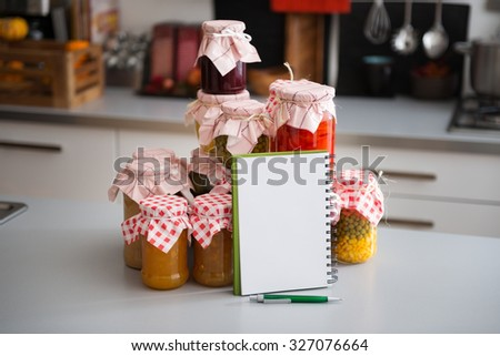A stack of glass jars filled with preserved vegetables is standing on the kitchen counter. Leaning up against them, a blank notebook, waiting to be filled with a list of all the delicious ingredients. - stock photo
