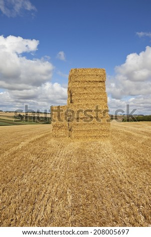 a stack of golden straw bales standing in a stubble field with scenic agricultural landscape under a blue cloudy sky in the yorkshire wolds