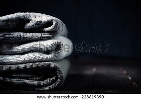 A stack of gray knitted winter sweaters on a dark background - stock photo