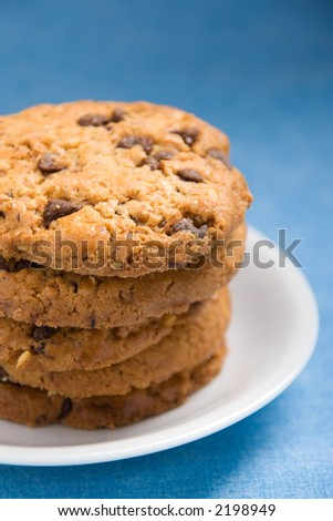 A stack of hazelnut and chocolate chips cookies on a white plate