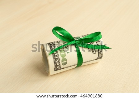 A stack of money with a ribbon. Expensive gift