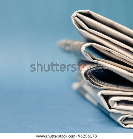 A stack of newspaper on blue background - stock photo